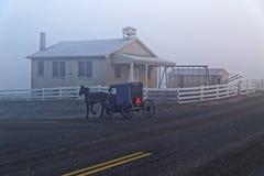 Um cavalo e um transporte passam uma casa da escola de Amish foto de stock royalty free