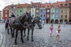 Um cavalo e um transporte esperam clientes para montar em torno das ruas coloridas de Poznan no Polônia Imagens de Stock Royalty Free