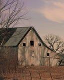Um celeiro de madeira cinzento em um monte íngreme no inverno fotografia de stock