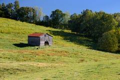 Um celeiro velho está no meio de uma exploração agrícola Foto de Stock Royalty Free