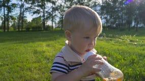 Um chá bebendo do rapaz pequeno de uma garrafa imagens de stock royalty free