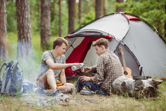 Um chá de derramamento da pessoa em seus amigos coloca ao acampar fotos de stock