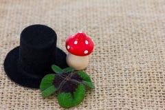 Um chapéu do cilindro, um cogumelo da mosca e trevo afortunado Fotos de Stock Royalty Free