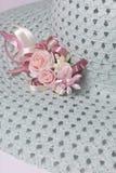Um chapéu fêmea largo-brimmed é leve - esverdeie, com uma casa de botão Flores artificiais sob a forma das rosas Fotos de Stock Royalty Free