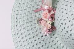 Um chapéu fêmea largo-brimmed é leve - esverdeie, com uma casa de botão Flores artificiais sob a forma das rosas Imagem de Stock Royalty Free
