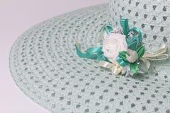 Um chapéu fêmea largo-brimmed é leve - esverdeie, com uma casa de botão Flores artificiais sob a forma das rosas Fotografia de Stock
