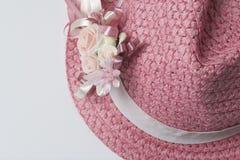 Um chapéu fêmea largo-brimmed da cor coral, decorado com uma casa de botão Flores artificiais sob a forma das rosas Imagem de Stock Royalty Free