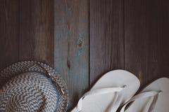 Um chapéu, uns óculos de sol e uns falhanços de aleta brancos na tabela de madeira foto de stock