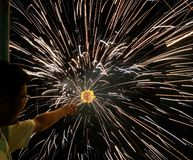 Um charki da mão da terra arrendada do homem, um fogo de artifício da mão que emite-se faíscas circulares no fundo preto foto de stock