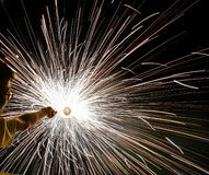 Um charki da mão da terra arrendada do homem, um fogo de artifício da mão que emite-se faíscas circulares no fundo preto fotografia de stock royalty free