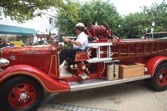 Um chefe dos bombeiros conduz um carro de bombeiros antigo fotografia de stock royalty free