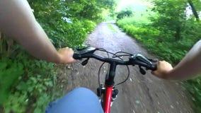Um ciclismo da pessoa em uma floresta decíduo rápida do passeio da bicicleta filme