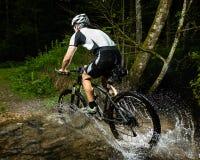 Um ciclista está conduzindo através da água Imagens de Stock Royalty Free