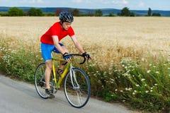 Um ciclista monta em uma bicicleta da estrada ao longo do campo Imagem de Stock