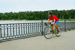 Um ciclista monta em uma bicicleta da estrada ao longo do lago Foto de Stock Royalty Free