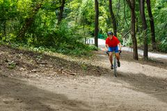 Um ciclista monta em uma bicicleta da estrada, indo acima monte Foto de Stock Royalty Free