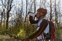Um ciclista no sportswear é água potável de uma garrafa foto de stock royalty free