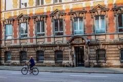 Um ciclista que monta uma bicicleta ao longo de uma rua Imagem de Stock
