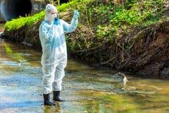 um cientista com uma amostra de ?gua contaminada contaminada com um Walkietalkie adverte sobre ambiental imagem de stock
