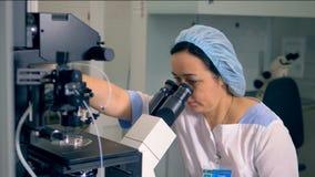 Um cientista fêmea está olhando na amostra do vírus através de um microscópio 4K vídeos de arquivo