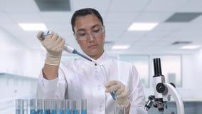 Um cientista fêmea examina uma amostra fluida azul usando um micropipette e os tubos de ensaio ao sentar-se em uma tabela no filme