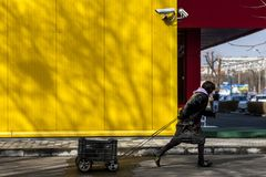 Um cigano com coisas roubadas ou encontradas vai após as câmeras de uma grande construção Fotos de Stock Royalty Free