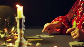 Um cigano em um bar da previsão do futuro pela luz de vela apresenta cartões para a adivinhação na tabela video estoque