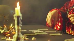 Um cigano em um bar da previsão do futuro pela luz de vela apresenta cartões para a adivinhação na tabela filme