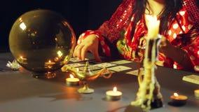 Um cigano em um bar da previsão do futuro pela luz de vela apresenta cartões para a adivinhação na tabela vídeos de arquivo