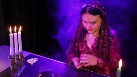 Um cigano em um vestido vermelho no fumo pela luz de vela lê o futuro nos mapas filme