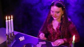 Um cigano em um vestido vermelho em um sal?o de beleza m?gico no fumo pela luz de vela l? o futuro nos cart?es filme