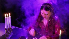 Um cigano em um vestido vermelho em um salão de beleza mágico no fumo pela luz de vela lê o futuro em pedras vídeos de arquivo