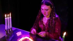 Um cigano novo cancela cartões antes da previsão do futuro sobre a bola de fogo mágica video estoque