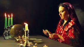 Um cigano novo em um bar da previsão do futuro pela luz de vela apresenta cartões para a adivinhação na tabela vídeos de arquivo