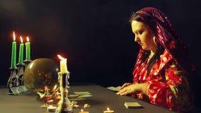 Um cigano novo em um bar da previsão do futuro pela luz de vela apresenta cartões para a adivinhação na tabela filme