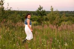 Um cigano novo que corre em um campo no por do sol foto de stock