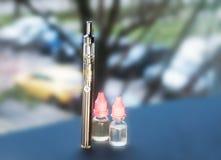 Um cigarro eletrônico, um vape, e diversas garrafas do líquido para reencher a mentira na janela Imagem de Stock