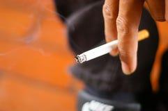 Um cigarro na mão do homem Imagens de Stock Royalty Free