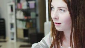 Um cliente novo, satisfeito bonito faz um tratamento de mãos em um salão de beleza video estoque