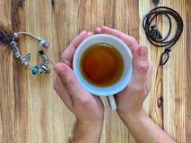 Um close up das mãos da mulher com os braceletes que guardam um copo do chá fotografia de stock