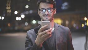Um close up de um homem com um telefone celular na noite na rua Fotografia de Stock Royalty Free