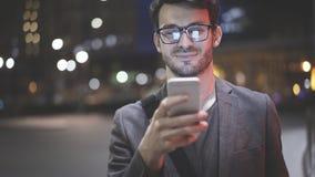 Um close up de um homem com um telefone celular na noite na rua Foto de Stock Royalty Free