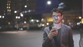 Um close up de um homem com um telefone celular na noite na rua Imagens de Stock Royalty Free