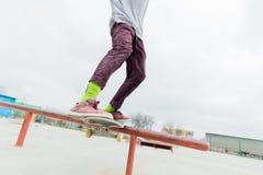 Um close-up de um pé do ` s do adolescente de um skater desliza em um skate ao longo dos trilhos no skatepark O conceito foto de stock royalty free