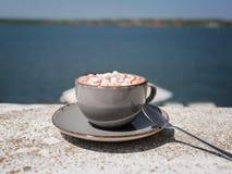 Um close-up de um chocolate quente com marshmallows em um fundo borrado do mar Uma bebida do cacau em um copo da porcelana cópia imagens de stock royalty free