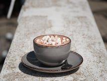 Um close-up de um copo do latte quente com marshmallows em um fundo de pedra gasto Uma bebida do cacau em um copo da porcelana foto de stock royalty free