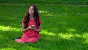 Um close-up de uma jovem mulher bonita que senta-se na grama Veste fones de ouvido e escuta a música S video estoque