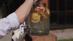 Um close-up de uma mão fêmea que agita uma bebida do verão usando uma colher filme