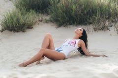 Um close-up de uma moça veio descansar, encontra-se na areia morna branca, aprecia o abrandamento, veste um roupa de banho branco fotografia de stock