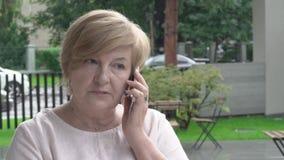 Um close up de uma mulher envelhecida bonita que fala sobre o telefone Está sentando-se fora no terraço filme
